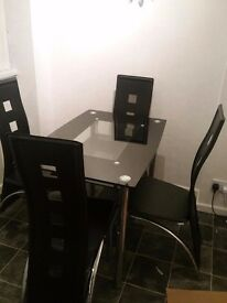 Black glass double tiered dining table and 4 stylish chairs