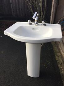 White basin with pedestal and chrome fittings