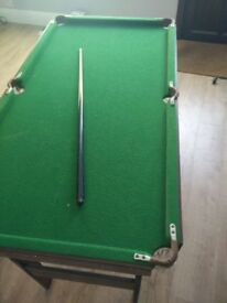 Pool table. Measures 138 x 74cm. Height: 80cm. One cue stick included. No balls. Collection only.