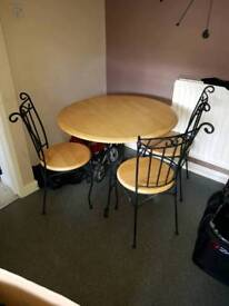 Round dinning room table and 4 chairs. Wooden tops diecast iron frame.