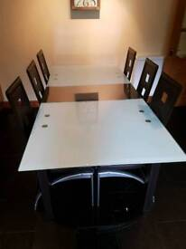 Extendable frosted table with brown leather chairs