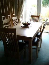 Solid oak extending dining room table and 8 chairs