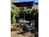 Grey/black garden table set with frosted glass top, parasol and 4 folding chairs.