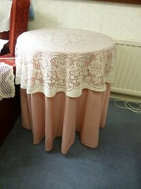 Small round table with tablecloth and lace topper