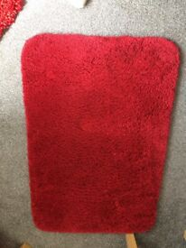 Two red rugs for sale.