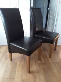 2 high back brown leather look dining room chairs.