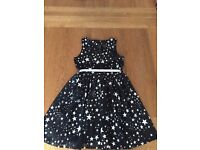 Girls M&S Black Dress covered with Silver Stars and has a Silver Belt. Age 7-8.