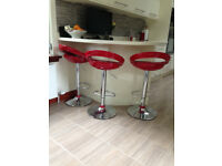 3 Deep Red Crescent shaped bar stools.