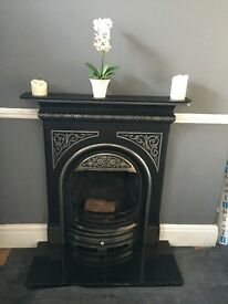 Cast iron fireplace with fire basket and hearth.