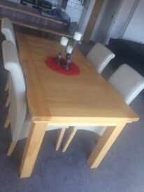 Dining table and cream faux leather chairs