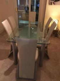 Glass Dining Table and 6 Cream Leather Chairs with silver on Table Legs and Chair Frames.