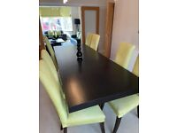 Black extendable dining table with eight high back chairs