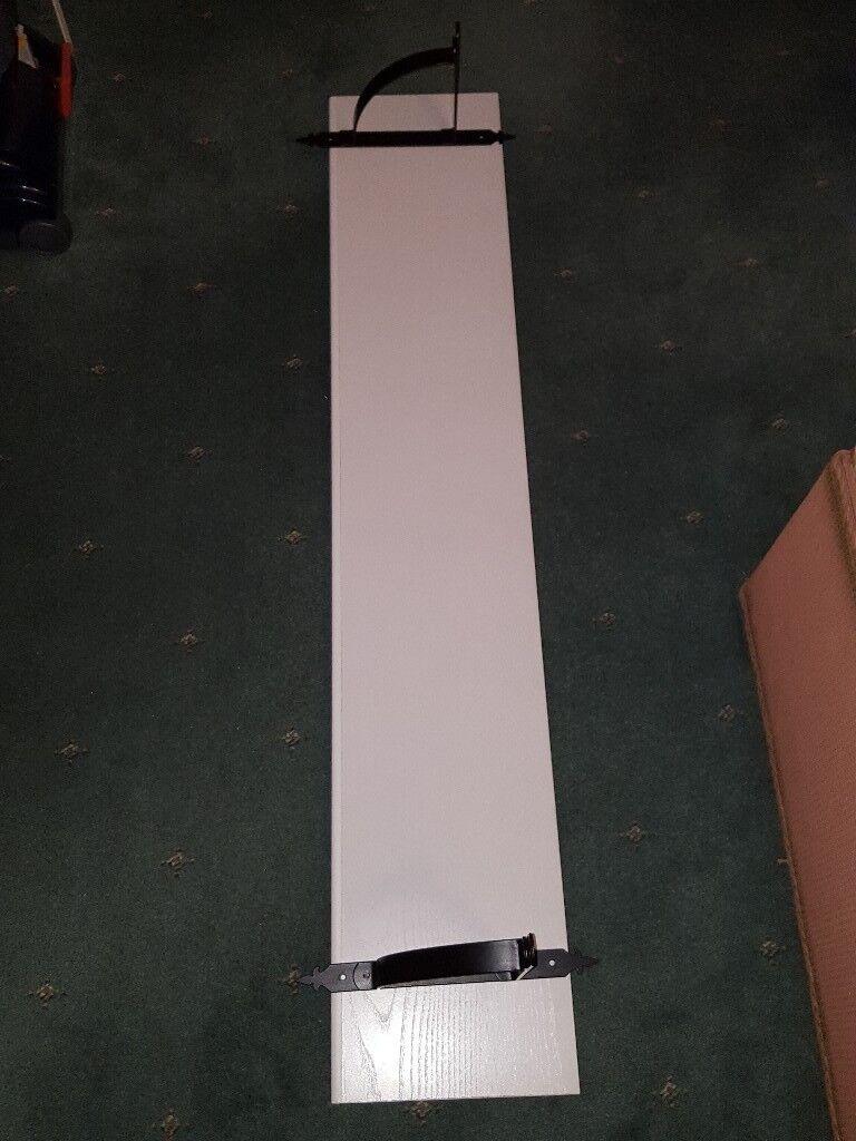 White wooden shelf with metal brackets
