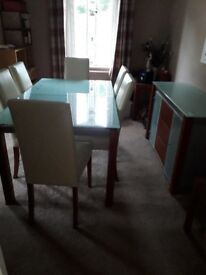 Glass dining table and 6 cream faux leather chairs and matching sideboard