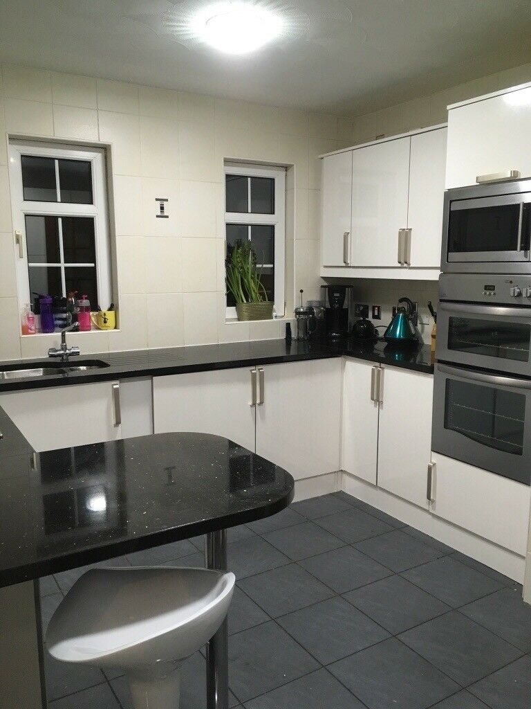 Whole White Gloss Kitchen With Black Granite Worktops In