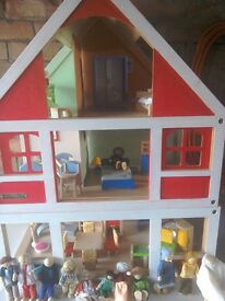Wooden 2storey dolls house with large selection of furniture and families. Good condition