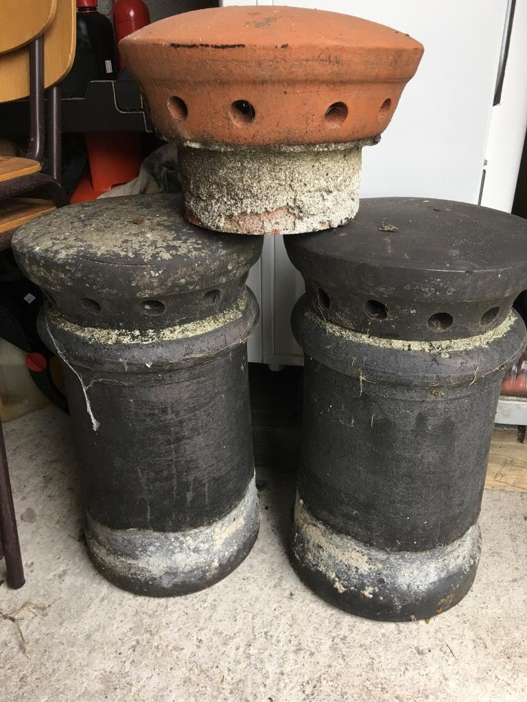 Two chimney pots with terracotta cowls and spare cowl