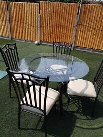 Glass dining table and 4 cream leather chairs