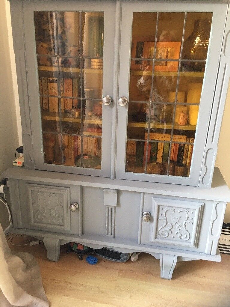 Vintage wall unit with glass inset doors .