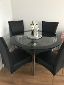 Harvey's Black and Clear Glass Dining Table with four chairs.