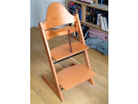 Stokke high chair, solid beech, very good condition. Includes bar and leather strap.