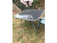 Glass top garden table and three matching chairs