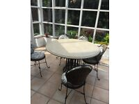 Conservatory/patio table, chairs, 2 seater couch armchair and footstool. Wrought iron with cushions.