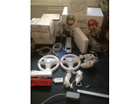 Boxed Nitendo Wii console,2 controllers,2 steering wheels,2 nunchucks and 26 premier titles