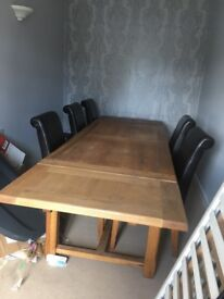 Solid oak 8 seater dining room table and brown high back leather chairs