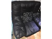 A black leather chair and a three seater settee.