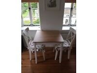 Wooden table with painted legs and matching white chairs