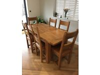 Solid oak extendable dining table with 6 matching leather seat chairs
