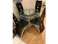 Circular glass dining room table with 4 chairs
