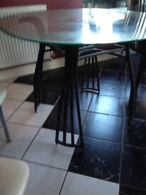 Glass/wrought iron 4-seater dining table. 3 X cream/chrome chairs (not matching)