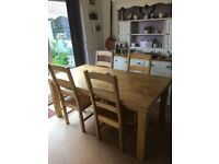 Large solid oak dining table and six matching chairs.