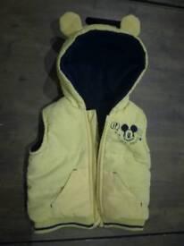 Unworn yellow 3-6m old body warmer.