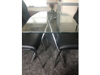 Glass dining table and 5 black high back chairs