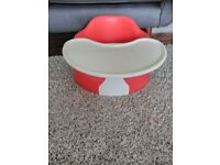 Red Bumbo seat with feeding/playing tray