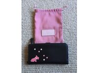 Black Radley purse with pink dog detail. Excellent condition, never used. Includes pink dust bag.