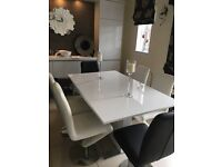 White gloss extendable dining table with 4 white & 2 black Z shaped chairs.