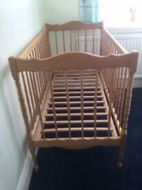 Wooden cot with turned side and end rails.