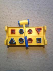 PLASTIC SHAPES SORTING TOY WITH FOUR SHAPES IN RED AND BLUE AND HAMMER.