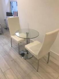 Glass dining table with two cream leather chairs