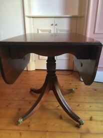 Small antique folding table with claw feet on castors