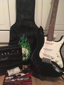 Black + white electric guitar with strap, case, amp, pedal, digital tuner and picks
