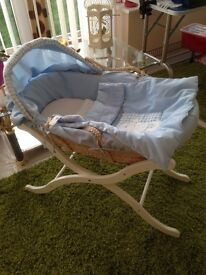 Moses basket and stand with some bedding.
