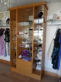 Mirror back display case unit with glass shelves and lighting.