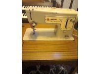 Retro Singer electric sewing machine in teak cabinet.
