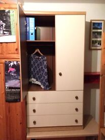 Childrens wardrobe with shelf and three drawers.