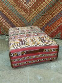 large ottoman coffee table upholstered in handmade vintage Moroccan Berber trimmed in old leather